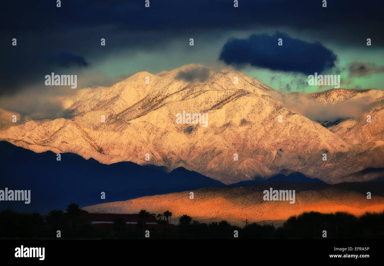 Snowcovered slopes of a mountain range with a dark stormy sky above, and a low sunlit cloud in the valley. - Stock Image