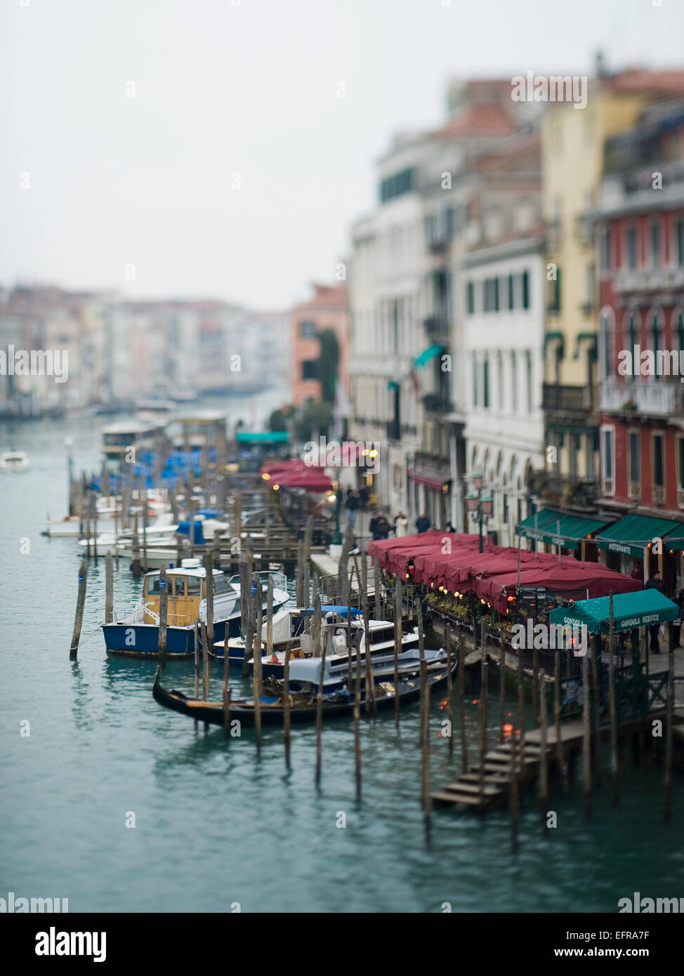 Wide canal in Venice, with boats and traditional gondolas moored along the waterfront, and restaurants and cafes. - Stock Image