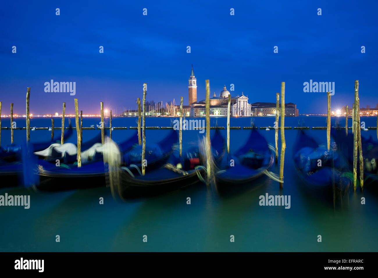 Riva degli Schiavoni and the Piazza San Marco island and church of San Giorgio Maggiore. Gondolas moored at dusk. - Stock Image