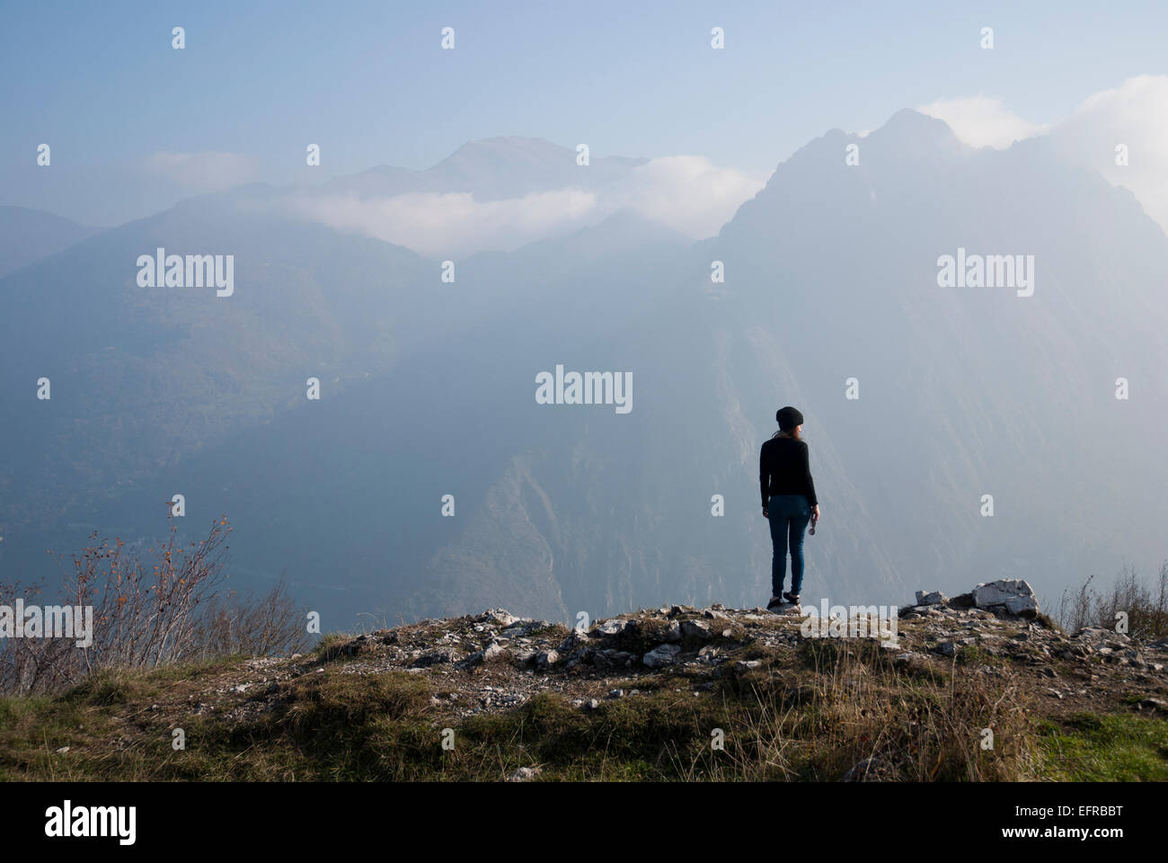 Woman standing on cliff at Lake Iseo, Italy - Stock Image