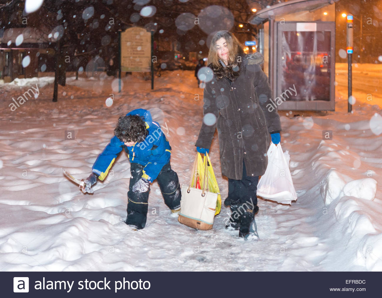 Everyday life of a single mother in Toronto during Winter, after work she picks up her kid,buys groceries and return - Stock Image