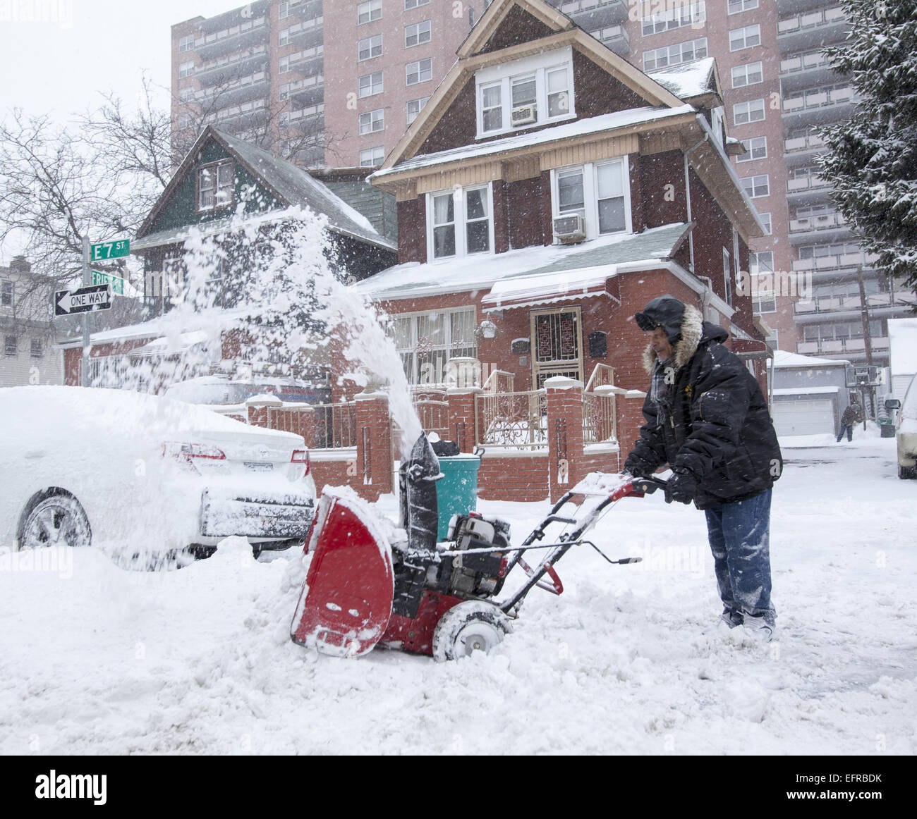 Man uses a snow blower after a heavy snow in the Kensington section of Brooklyn, NY. - Stock Image