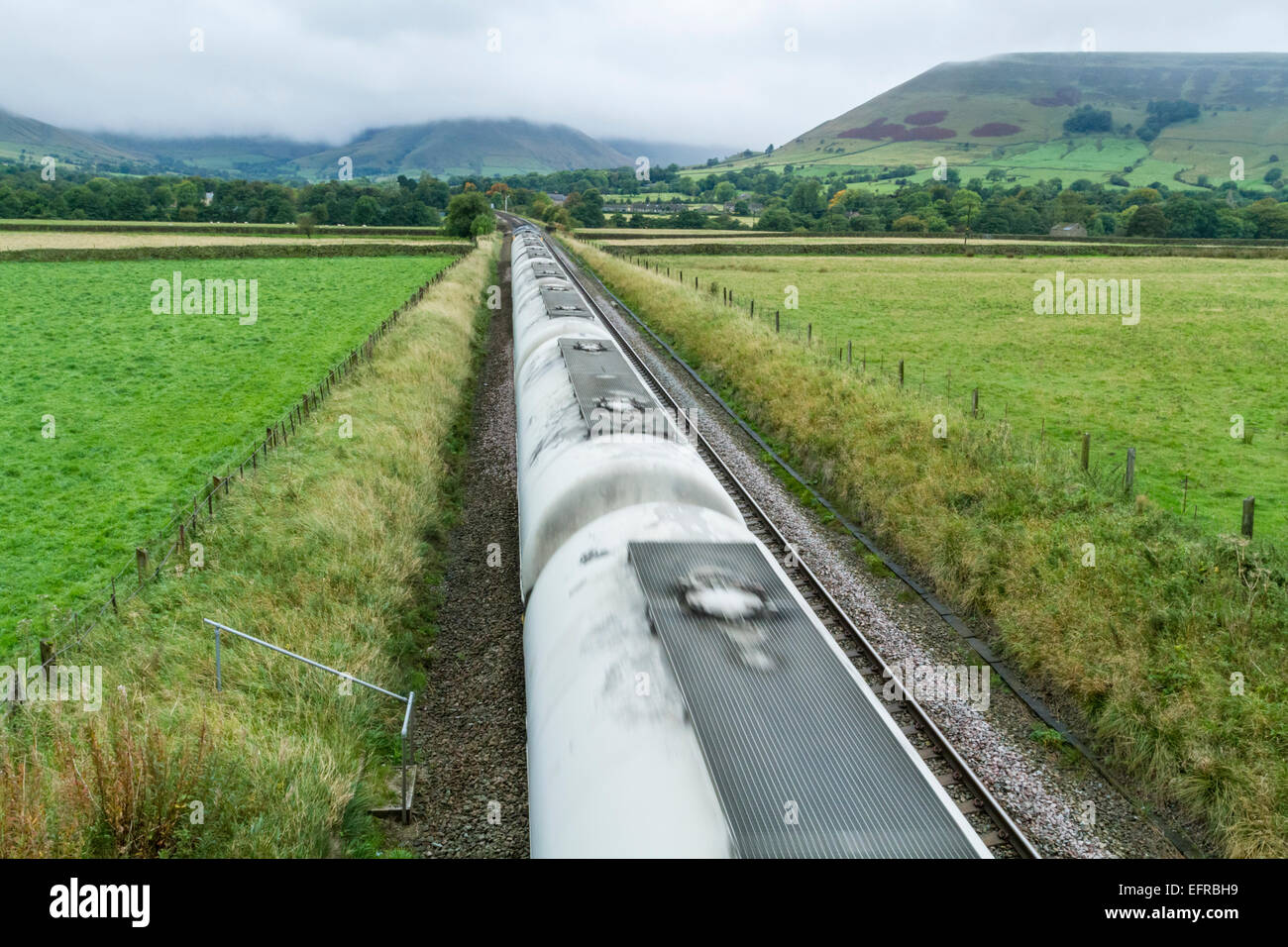 Freight train carrying cement passing through the countryside in Derbyshire, Peak District National Park, England, - Stock Image