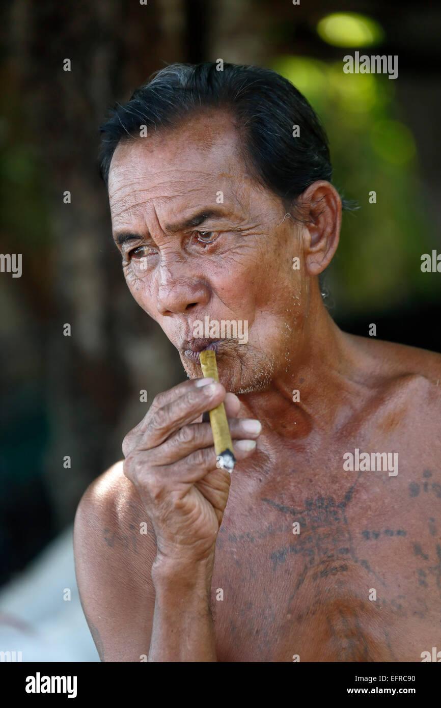 Mulberry (saa) paper artisan smoking a cigar, near Chiang Mai, Thailand - Stock Image
