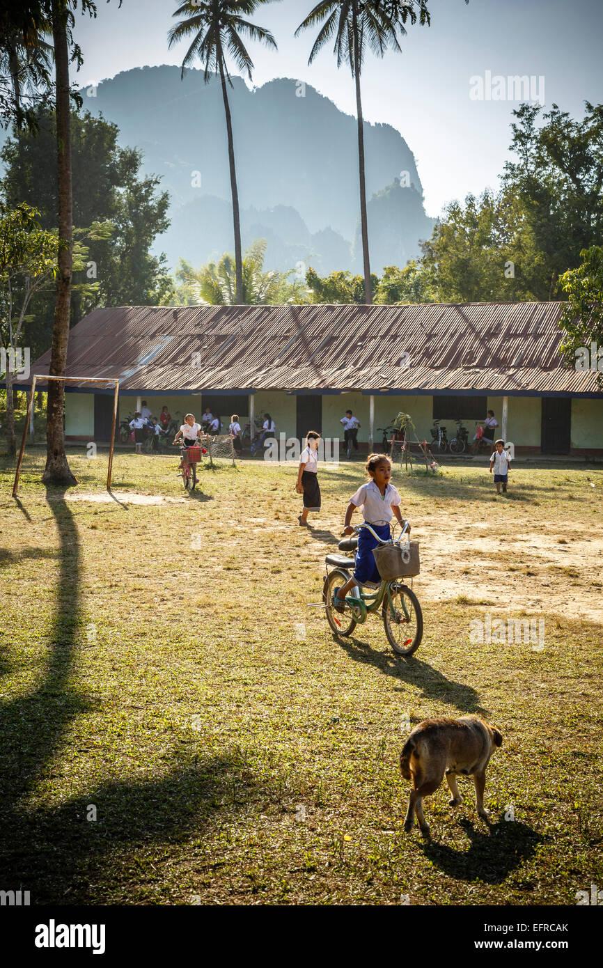 School children riding a bicycle, Vang Vieng, Laos. - Stock Image