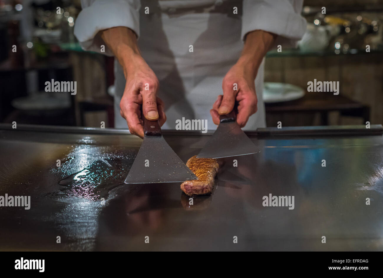 Chef cooking wagyu beef in Japanese teppanyaki restaurant, Tokyo, very shallow focus Stock Photo