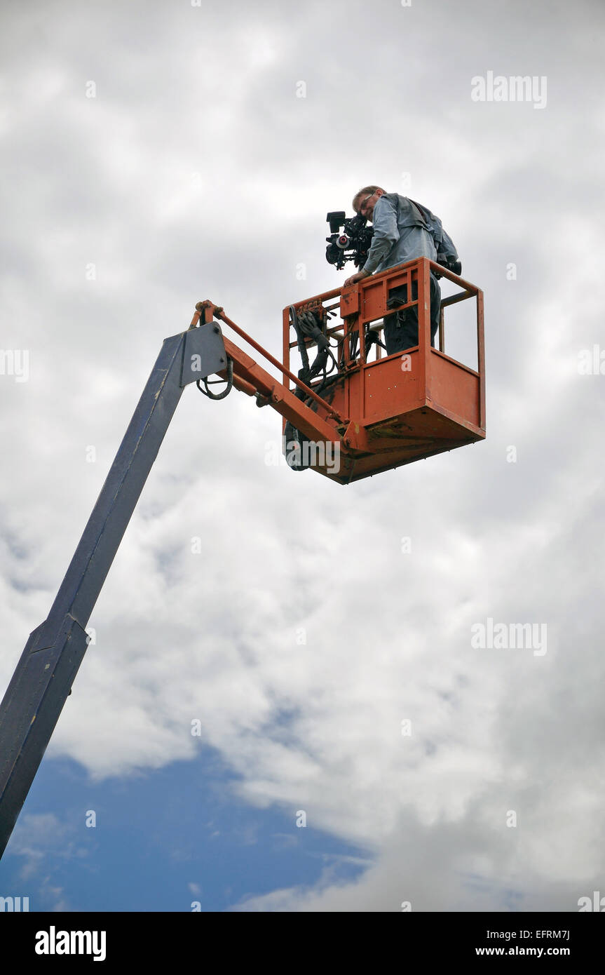 Cameraman using a cherry picker on location - Stock Image