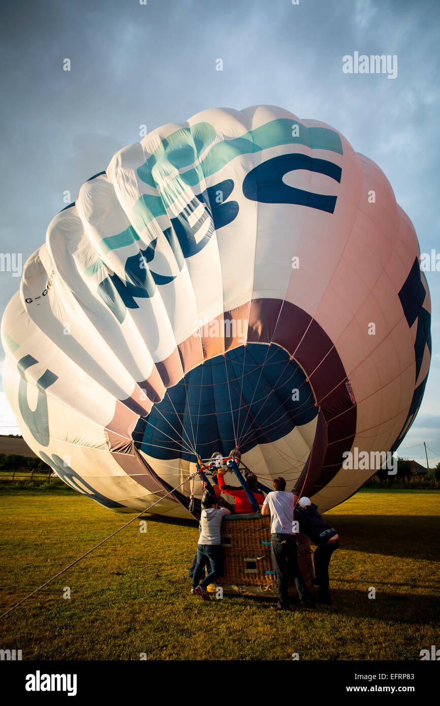 Crew inflating hot air balloon at sunset, South Oxfordshire, England Stock Photo