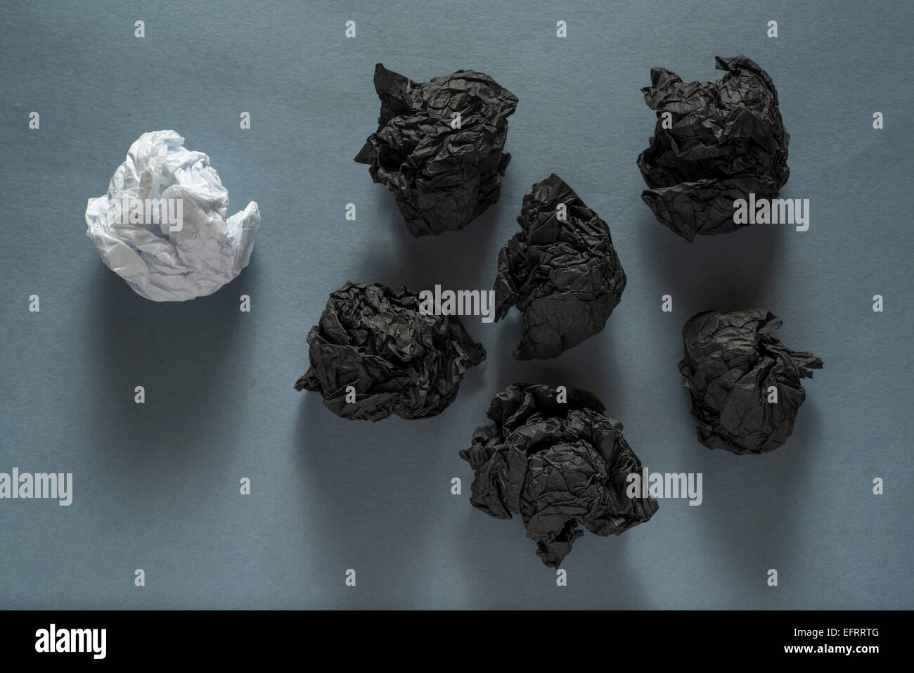 black crumpled paper ball and different white crumpled paper ball on a grey background - Stock Image