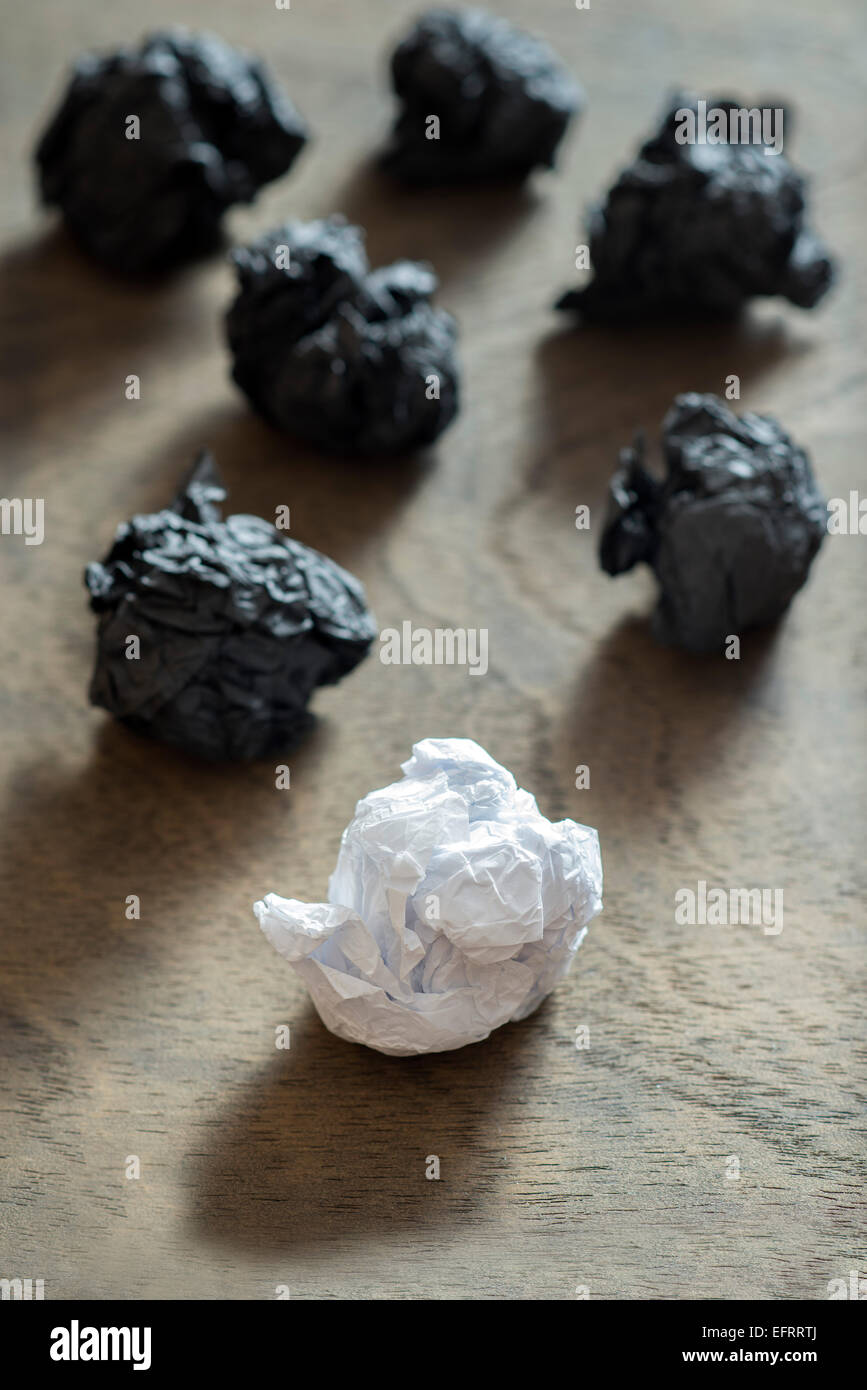 black crumpled paper ball and different white crumpled paper ball on a wooden background - Stock Image