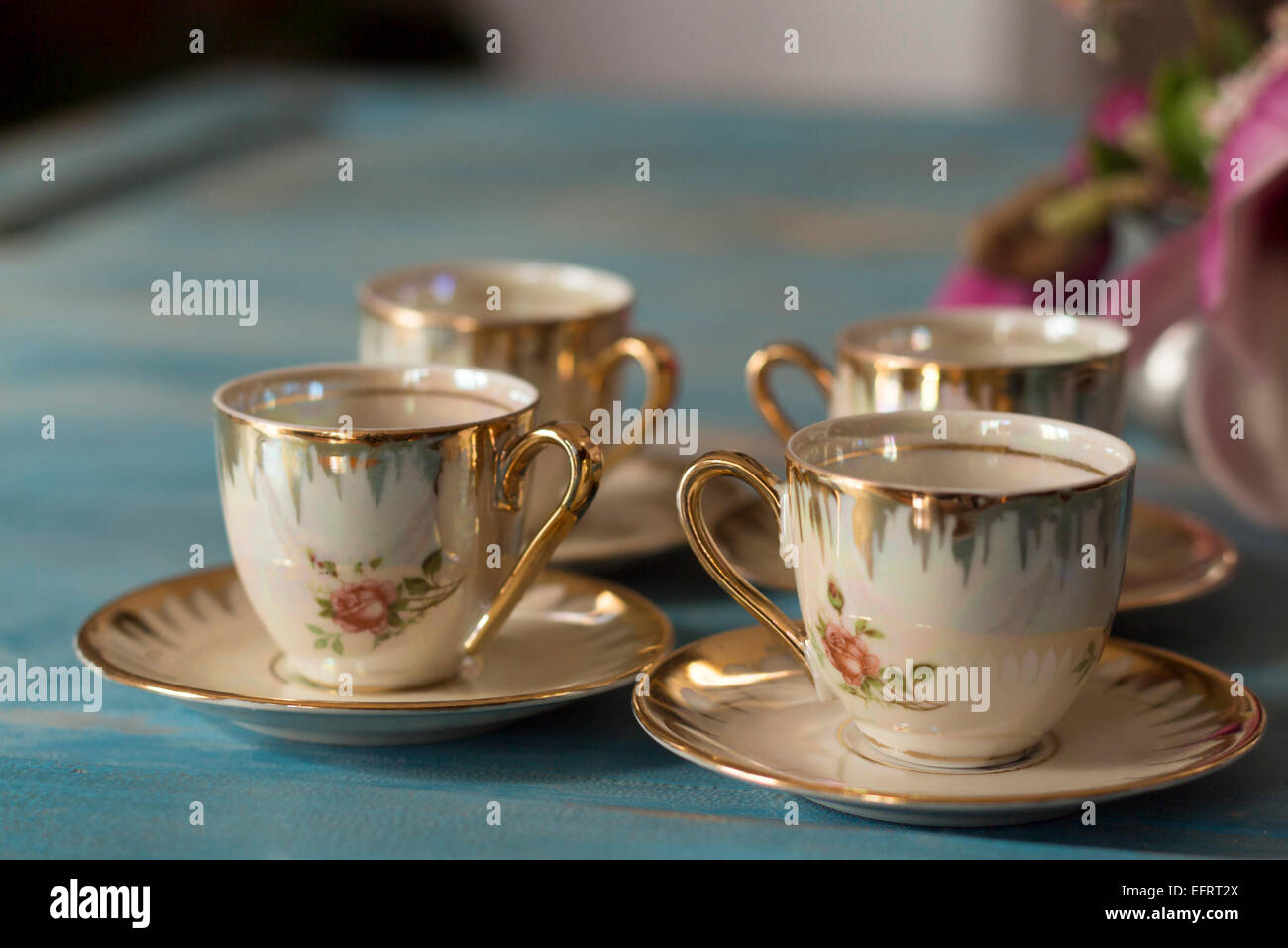 Vintage tea cups with saucers on old wooden table. - Stock Image