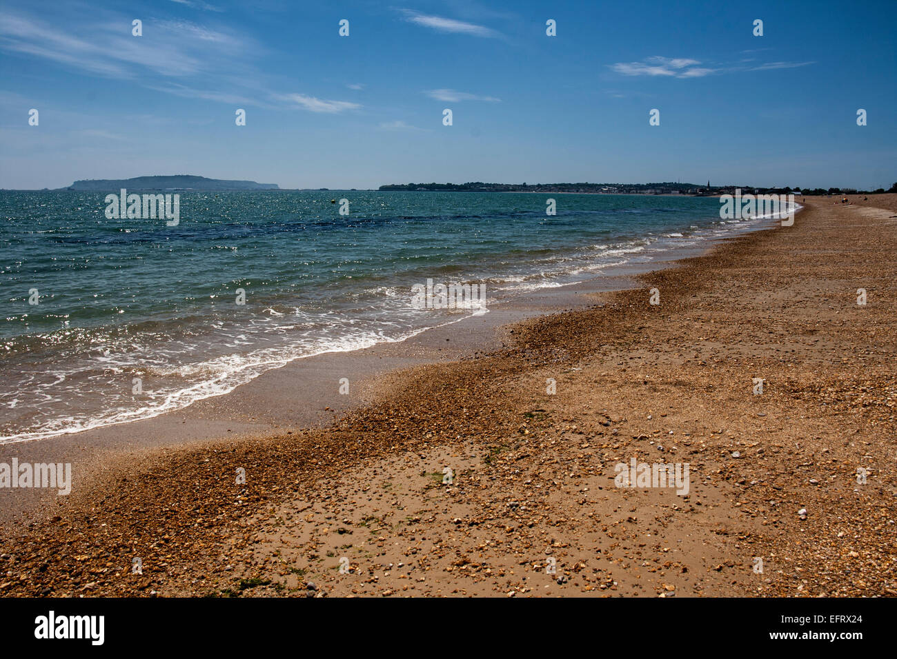 stony beach in the summer with blue sea and sky - Stock Image