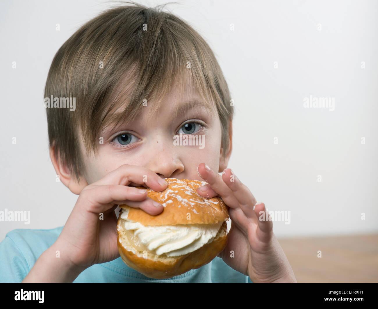 Young boy eating a tasty cream bun - Stock Image