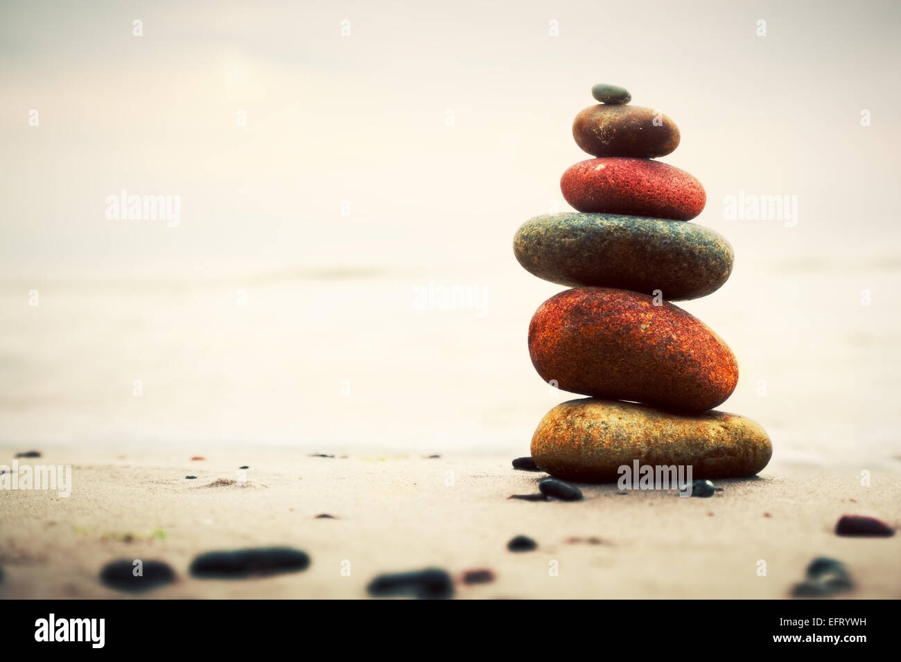 Stones pyramid on sand symbolizing zen, harmony, balance. Ocean in the background Stock Photo
