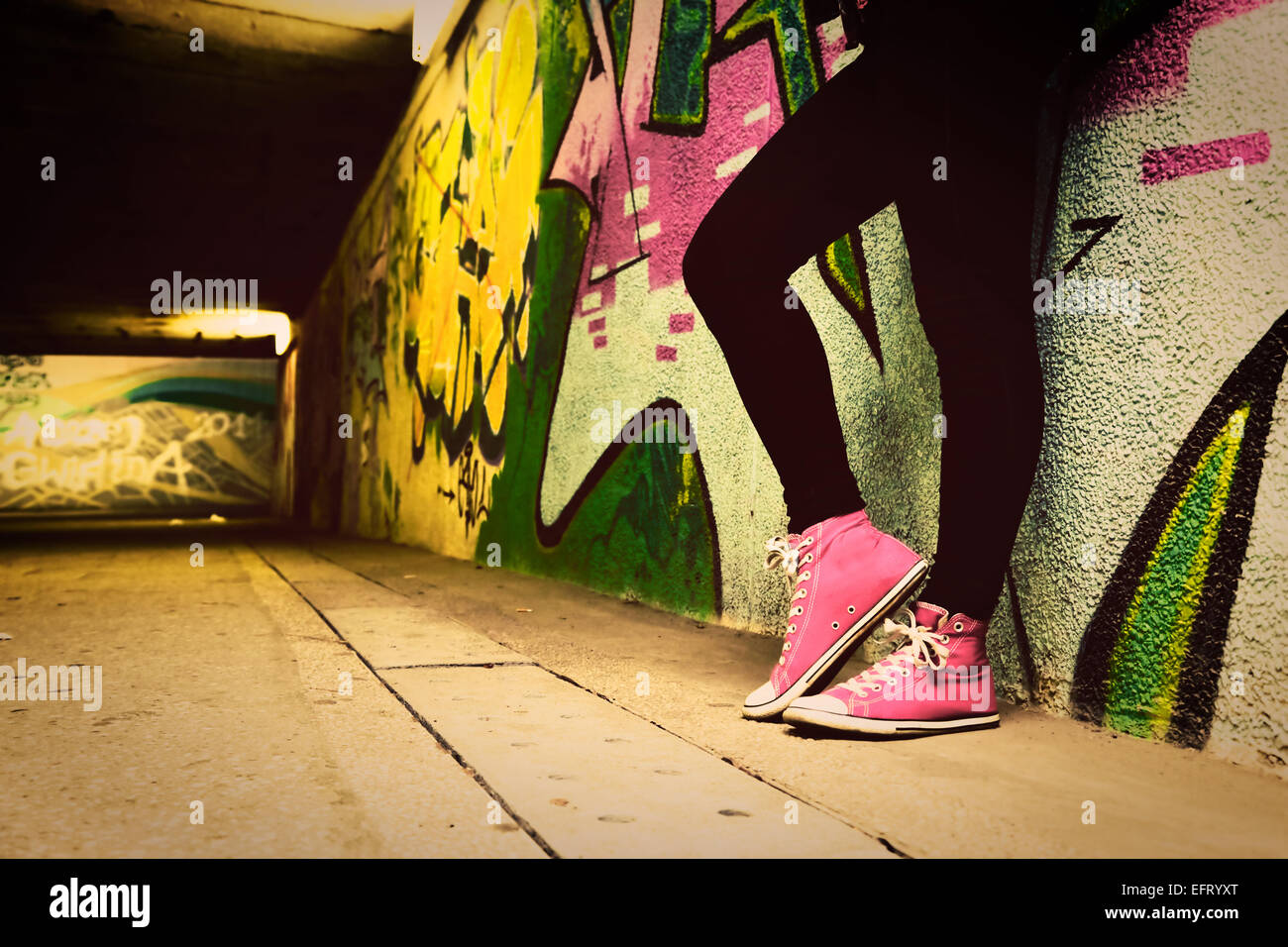 Close up of pink sneakers worn by a teenager. Grunge graffiti wall ...