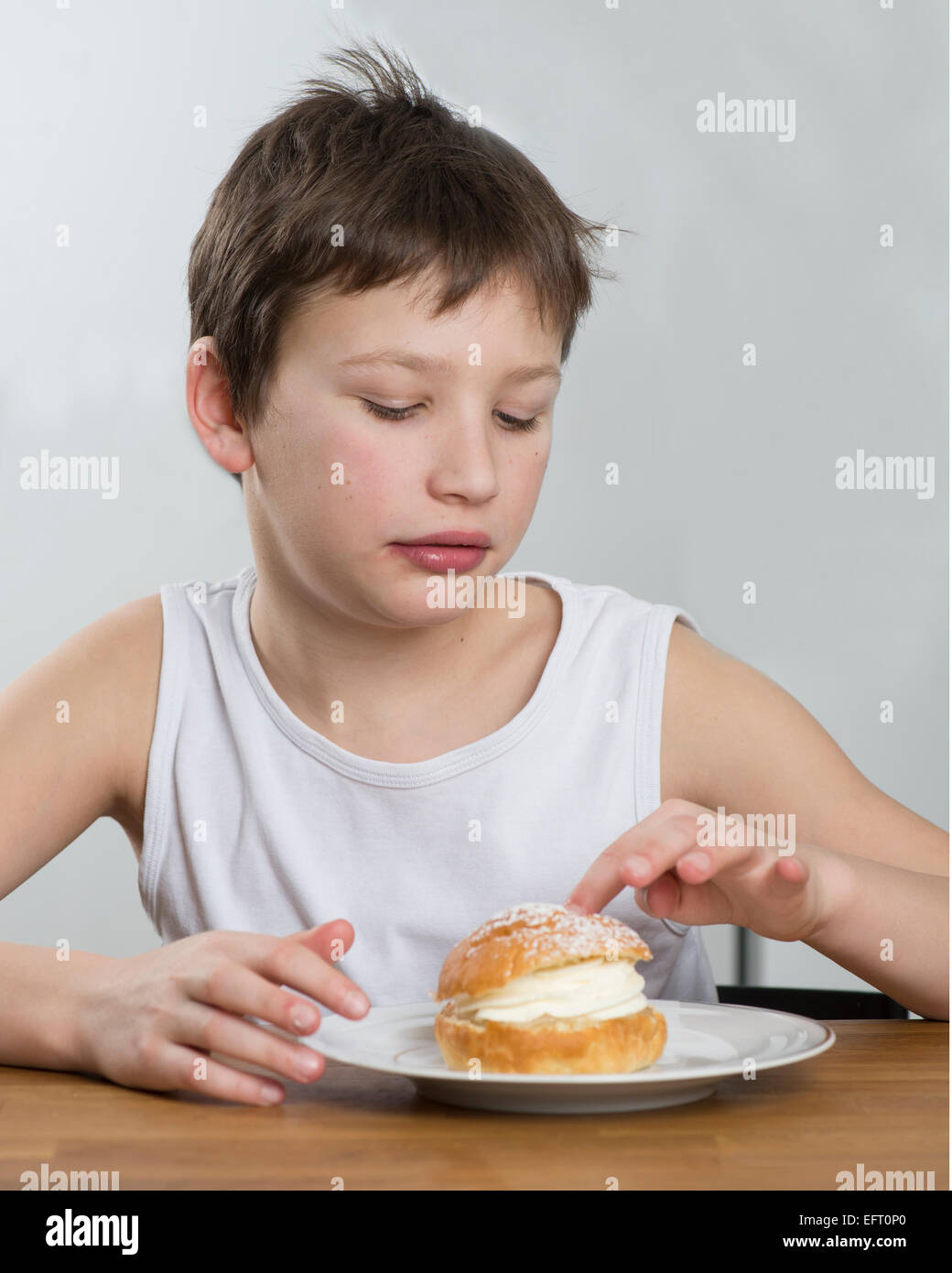 Young boy with a tasty cream bun - Stock Image