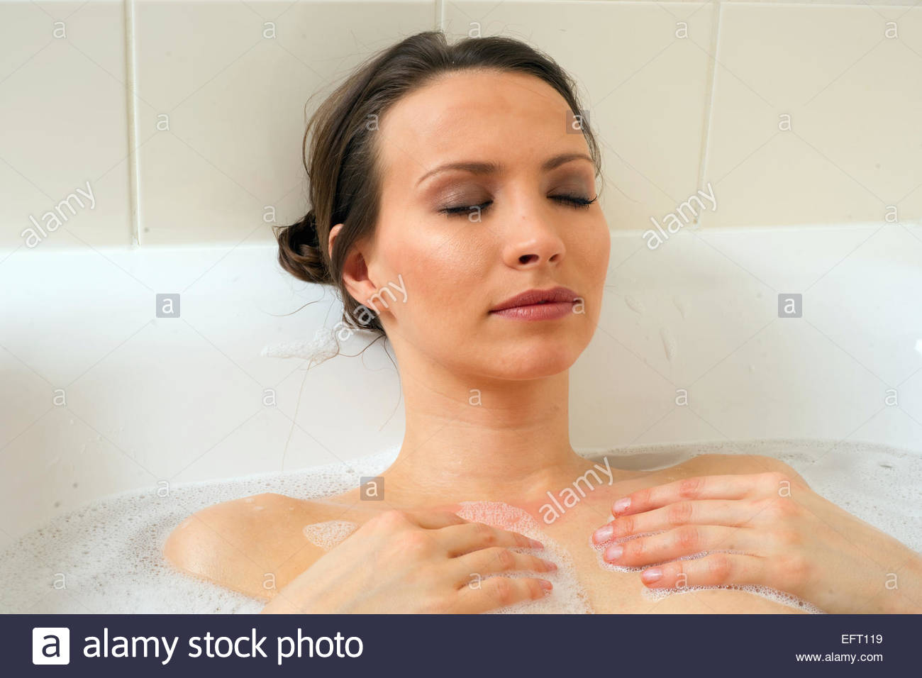 Young Bathing In A Bathtub Bathroom Washing Face Woman Bathtub Lifestyle Portrait Young Adult One Person Only Young - Stock Image