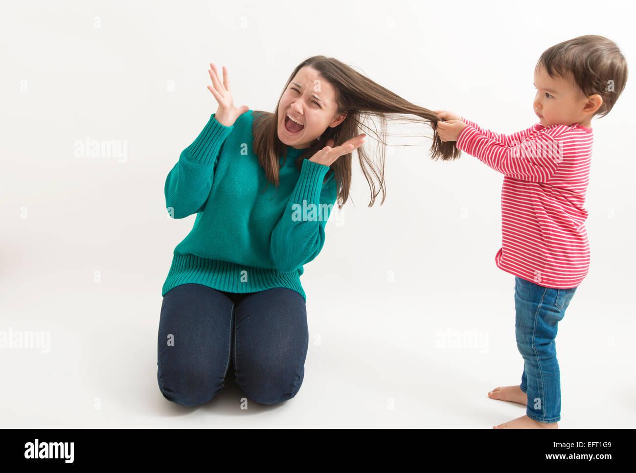 little girl pulls her older sister's hair Stock Photo