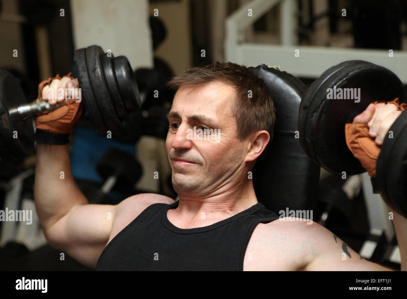 training dumbbells in gym  Male lifting weights for upper