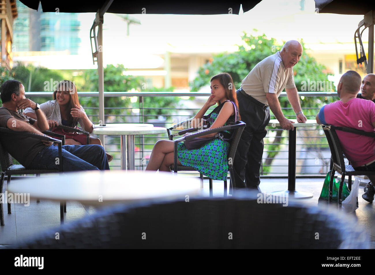 Filipinas socialising with foreigners at Bo's Coffee House the Terraces Ayala Center Cebu City Philippines - Stock Image