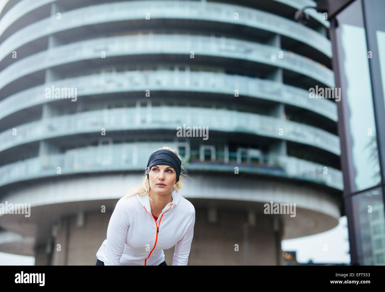 Athlete having a short break from running. Young female exercising on city street. - Stock Image