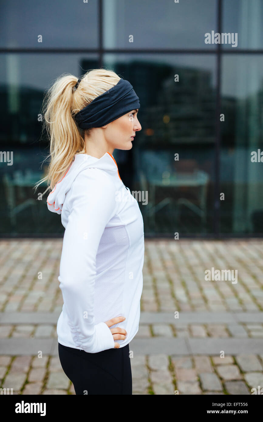 Side view of young sporty woman standing with her hands on hips outdoors. Caucasian female athlete on street preparing - Stock Image