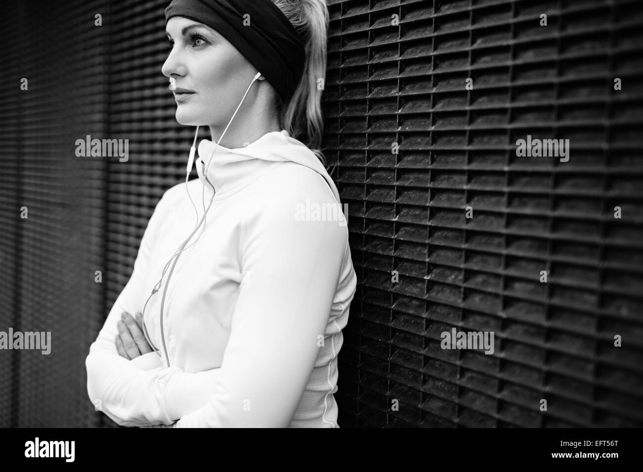 Black and white image of young woman wearing earphones standing leaning a wall looking away confidently. Fitness - Stock Image