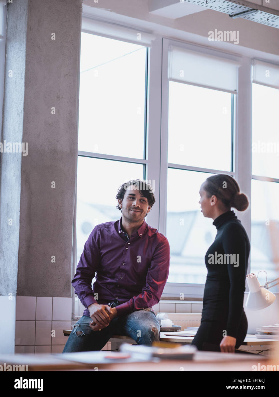 Indoor shot of young people talking in office. Executives discussing work. - Stock Image