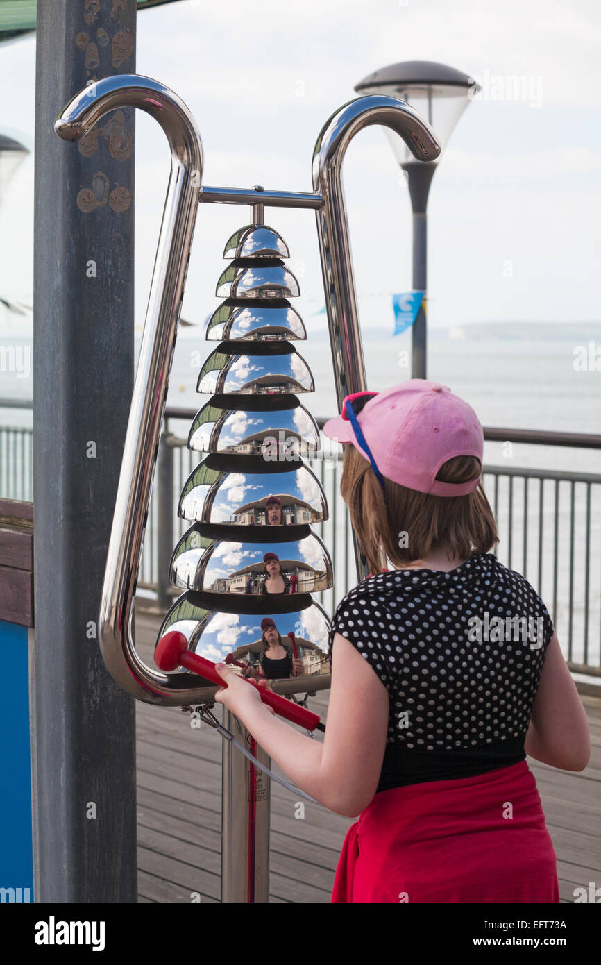 Young girl playing Bell Lyre percussion instruments with reflections on Boscombe pier in April - Stock Image