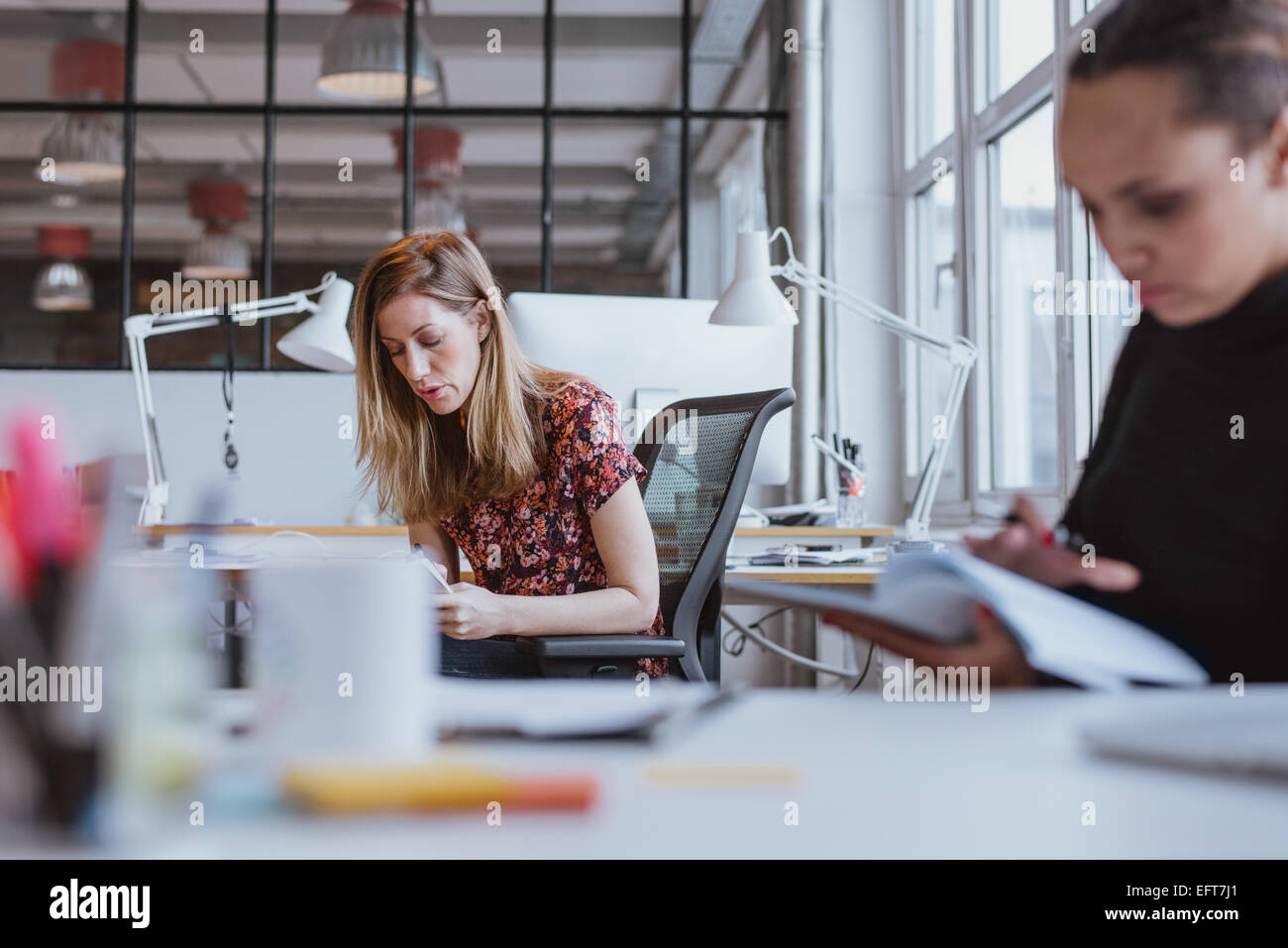 Image of young woman busy working at her desk with coworker reading a report in front. - Stock Image