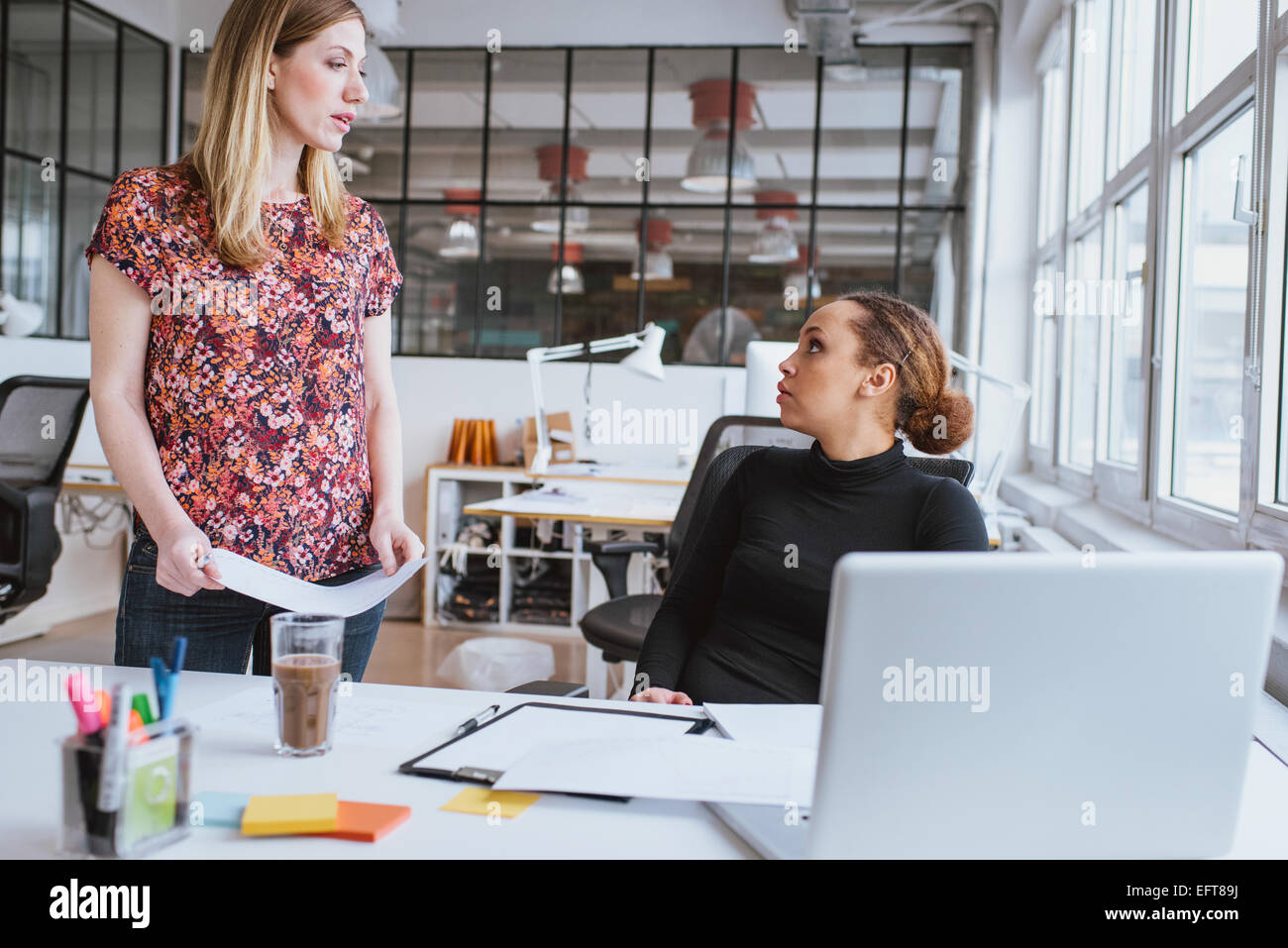 Young woman discussing work with colleague. Two young businesswoman at office. - Stock Image