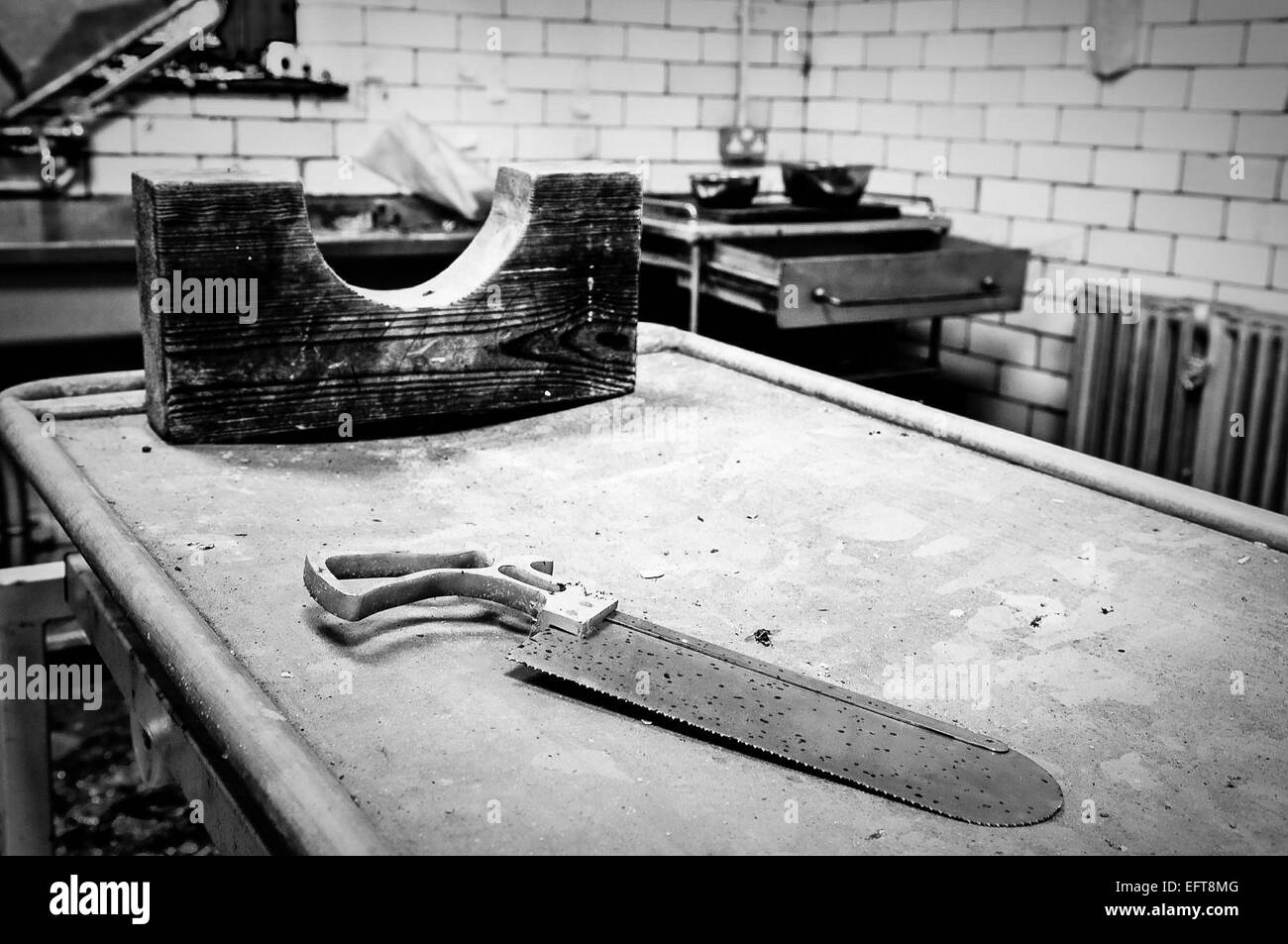 Mortician's saw and wooden neck brace on a preparation table. - Stock Image