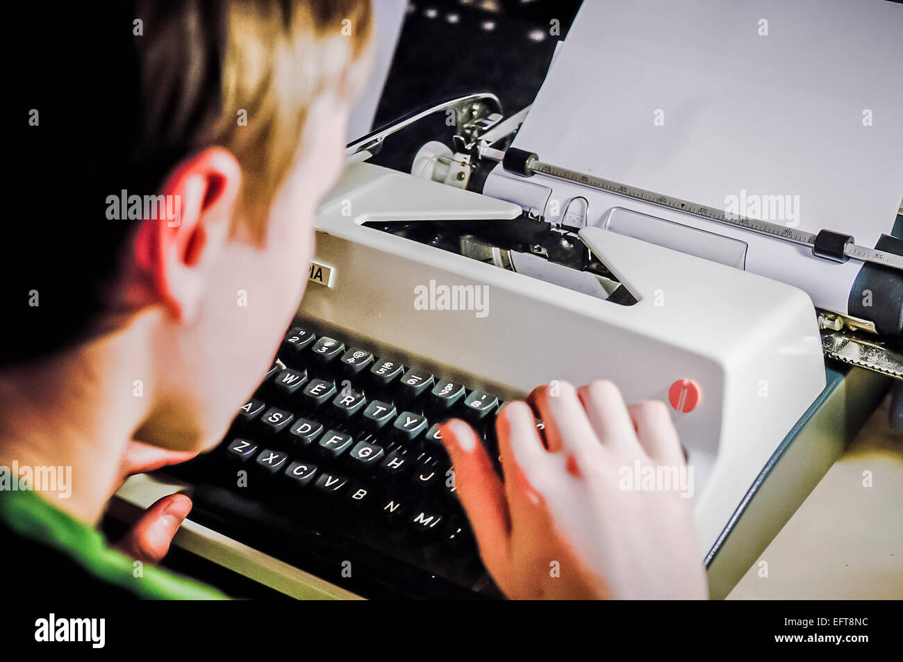 Boy types on an old fashioned mechanical typerighter. - Stock Image