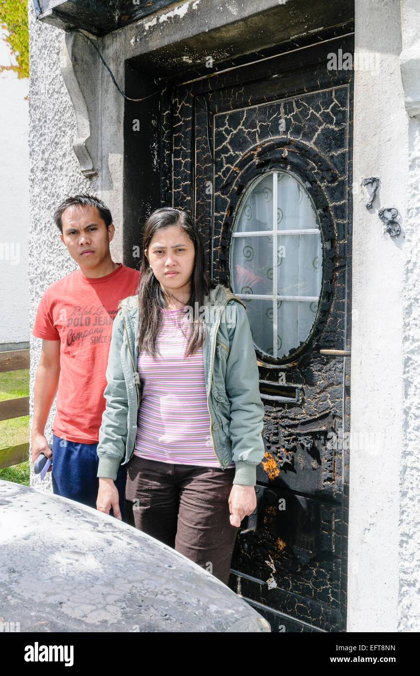 Belfast, Northern Ireland. 22 Jun 2010. An Indonesian couple stand in front of their door following a racist and - Stock Image