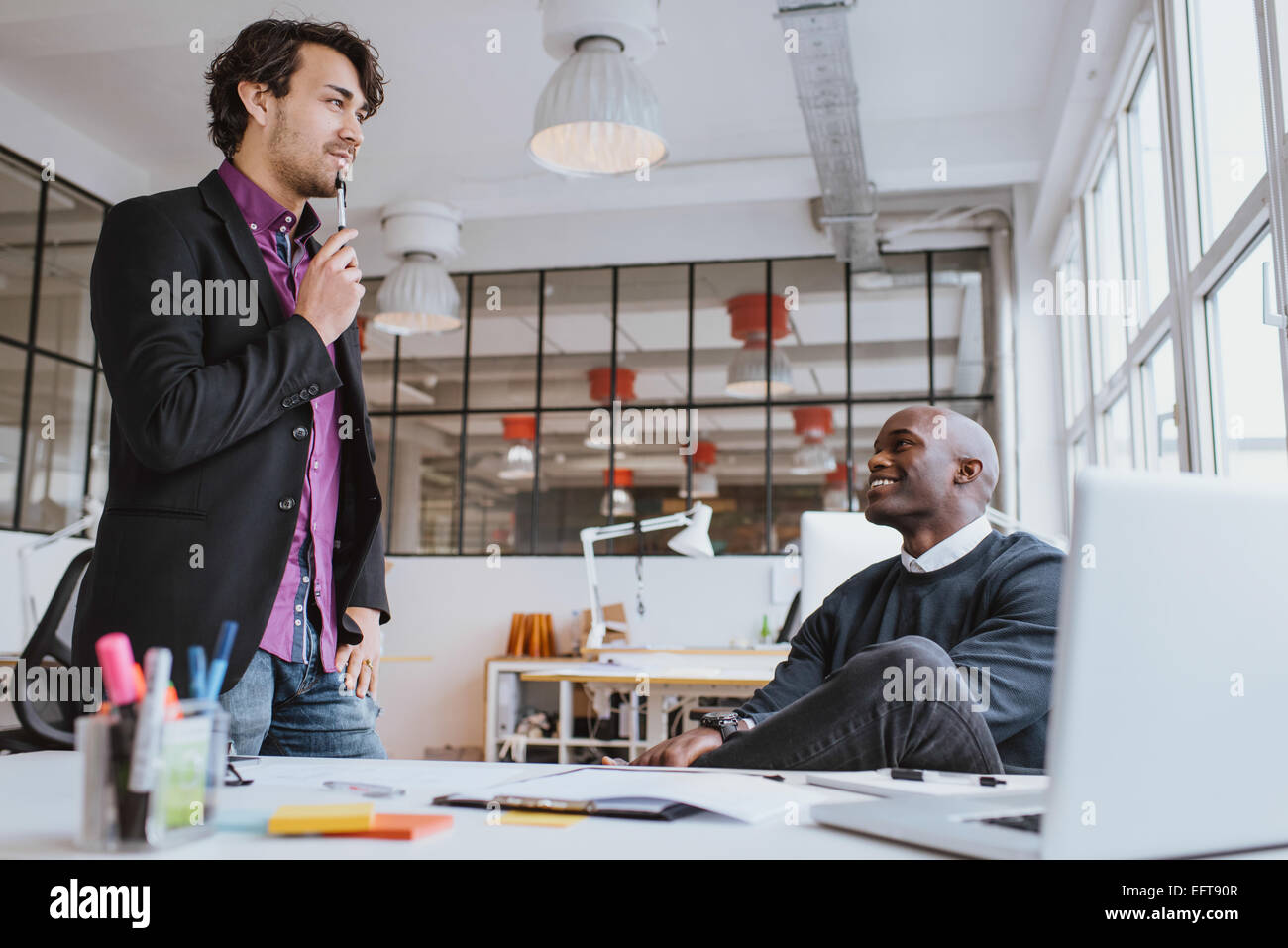 Two young office workers discussing work in office. Office manager with colleague. - Stock Image