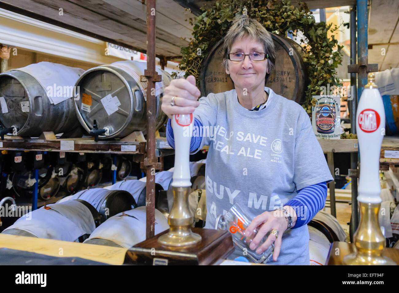 A woman pulls a pint of beer at a CAMRA real ale festival. - Stock Image