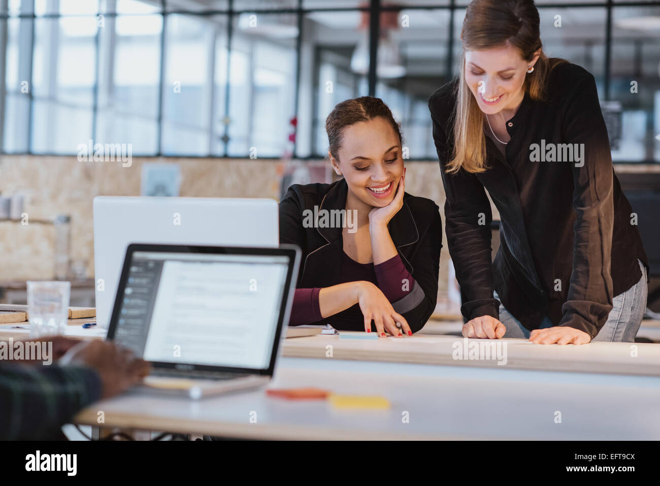 Two young woman at office working on a new creative design. Diverse team of professionals looking at a document - Stock Image