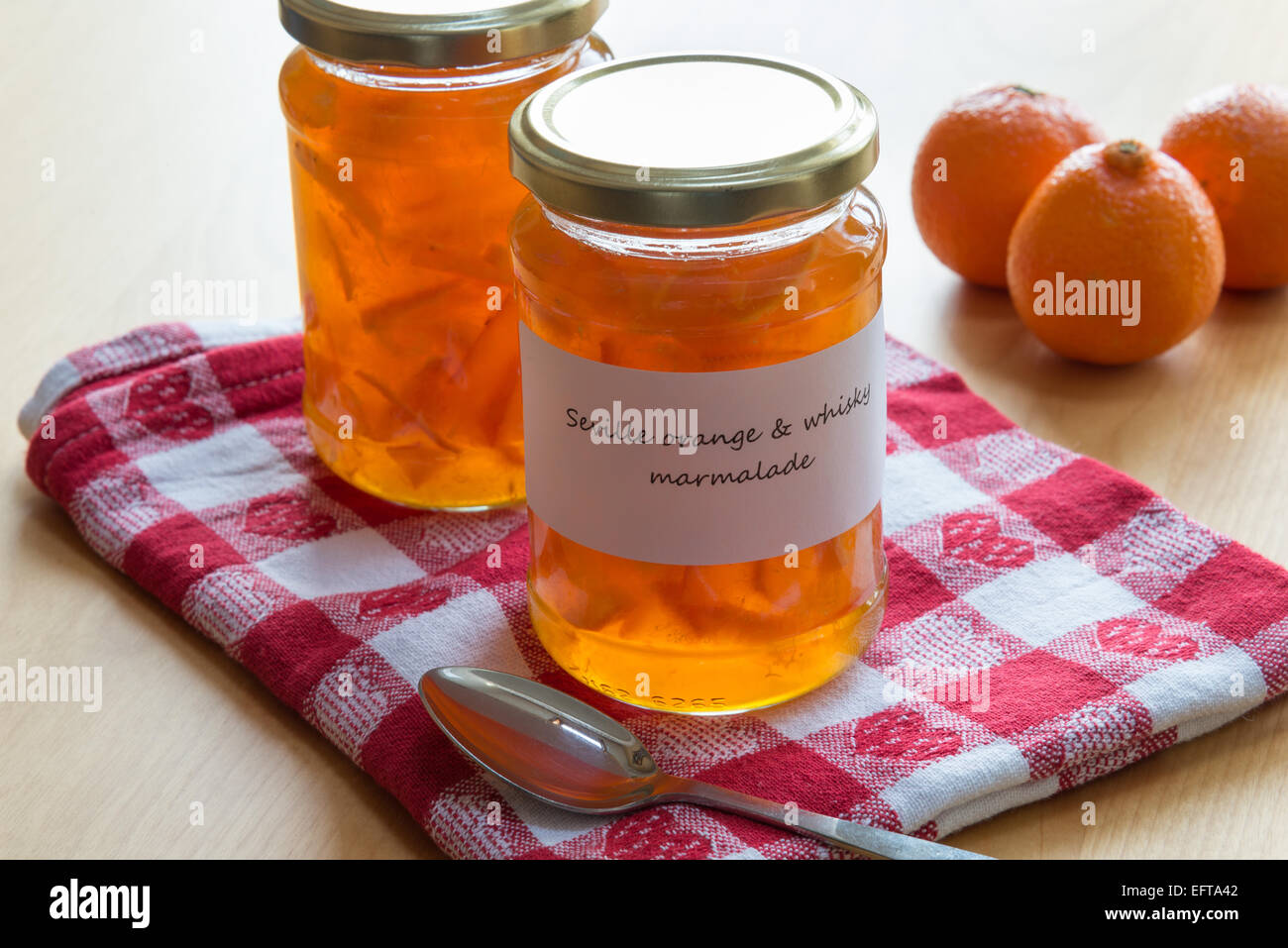 Jars of homemade Seville orange and whisky marmalade. - Stock Image