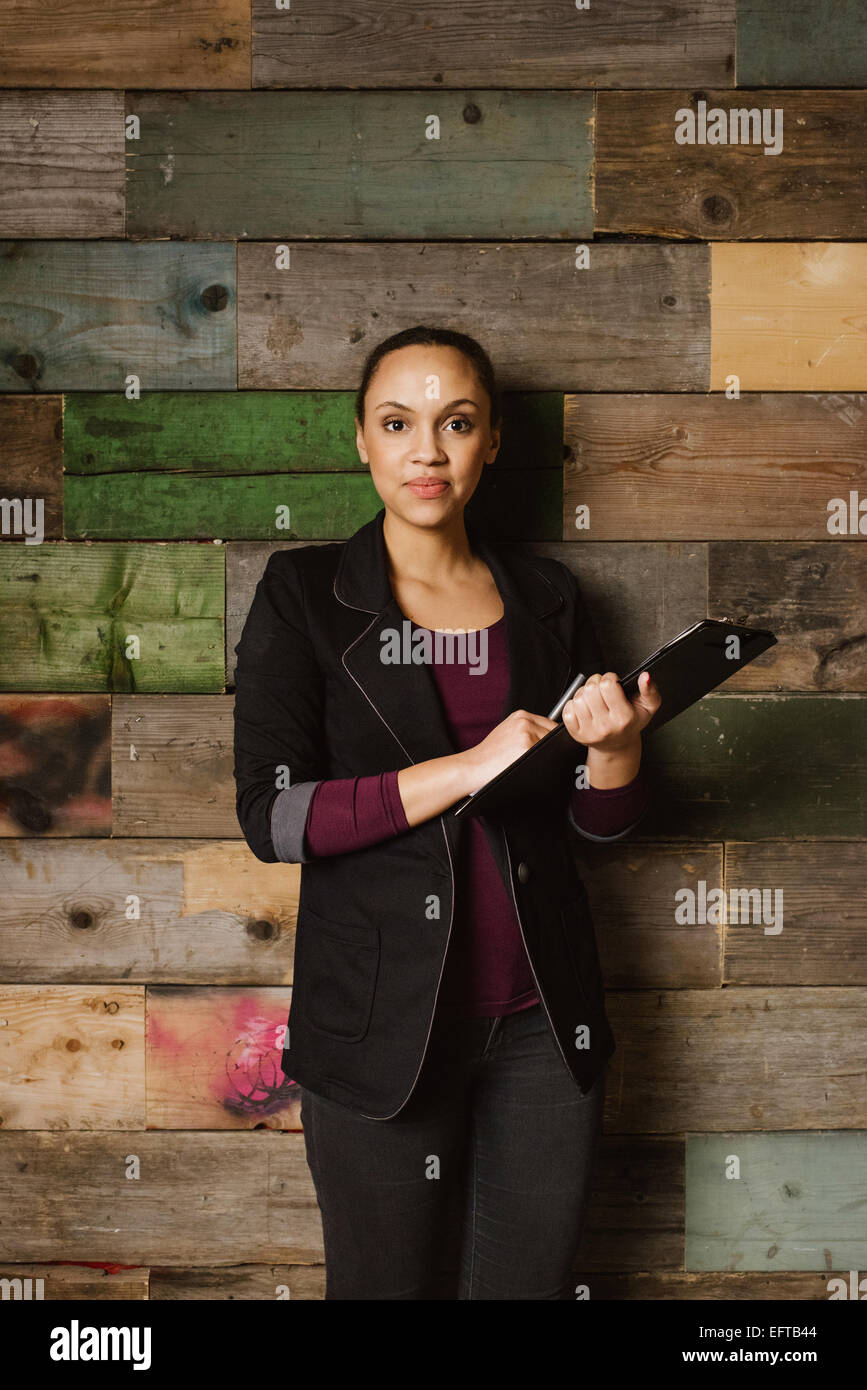 Portrait of confident young african businesswoman standing against wooden wall in office holding a clipboard. - Stock Image