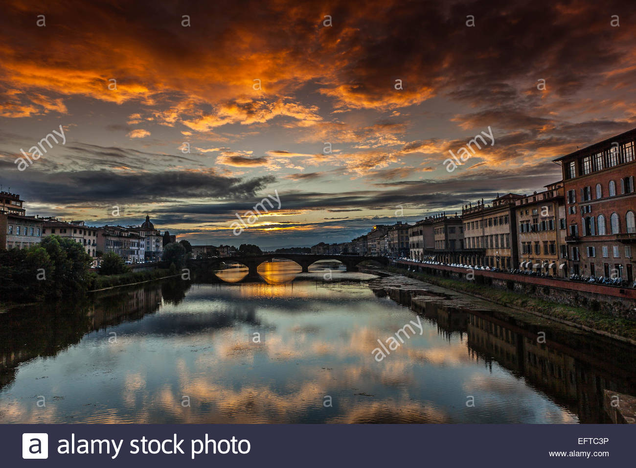 Moody sky reflecting in still city river - Stock Image