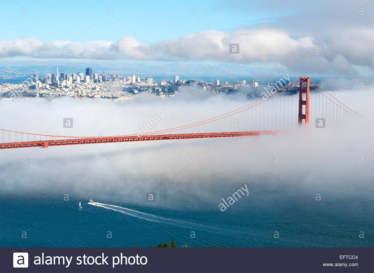 Golden Gate Bridge in thick fog and waterfront cityscape in background - Stock Image