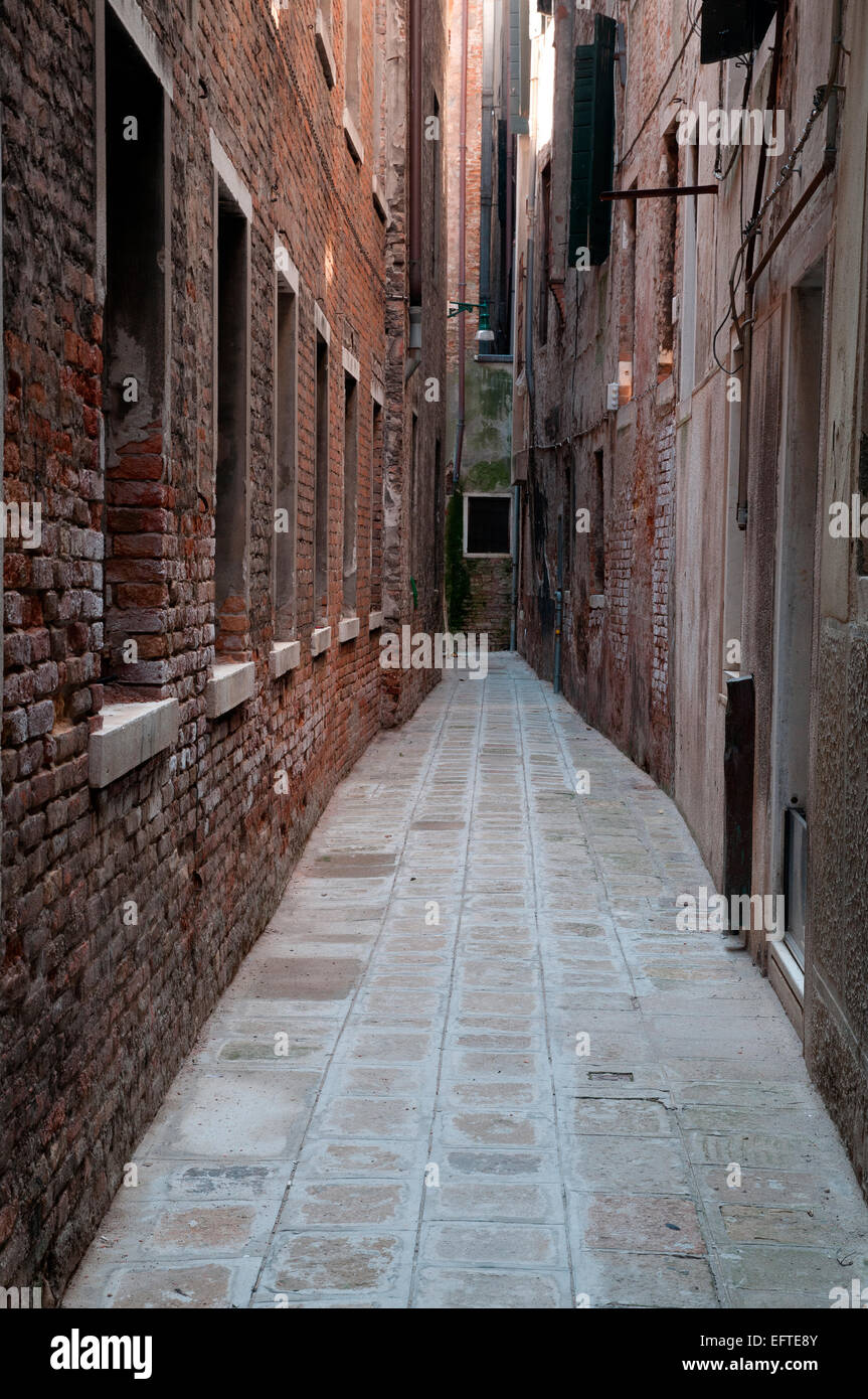 A typical very narrow passageway or Calle off Calle Ostraghe in old Venice Italy - Stock Image