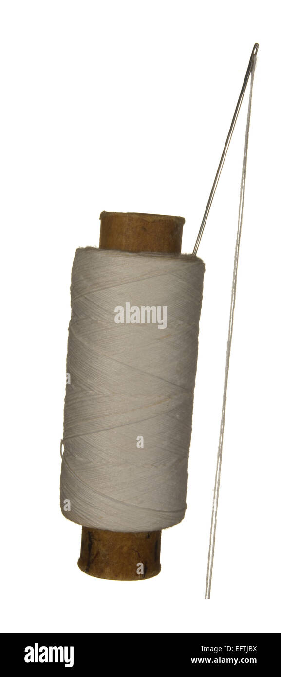 Spool of white thread and needle isolated on white background. - Stock Image