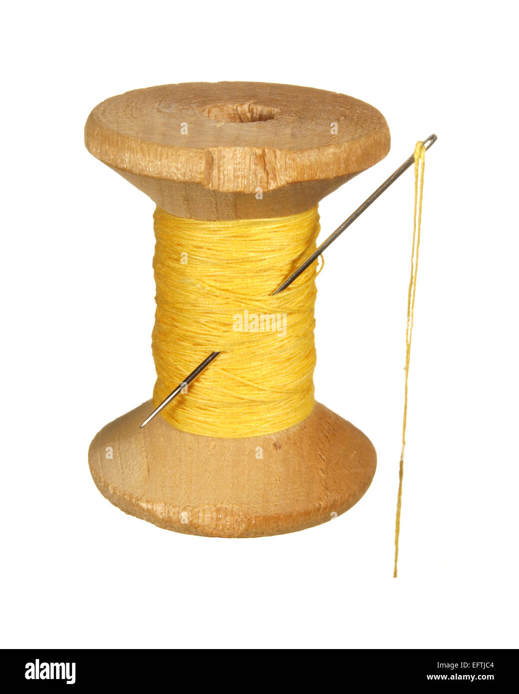 Old wooden spool of yellow thread and needle isolated on white background. - Stock Image
