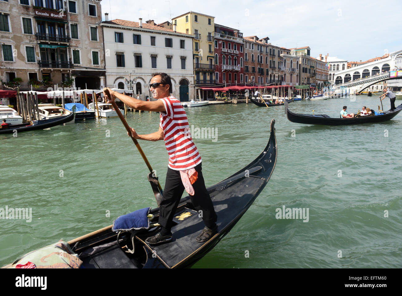 Gondolier steers his gondola up and down the Grand Canal, Venice Italy. - Stock Image