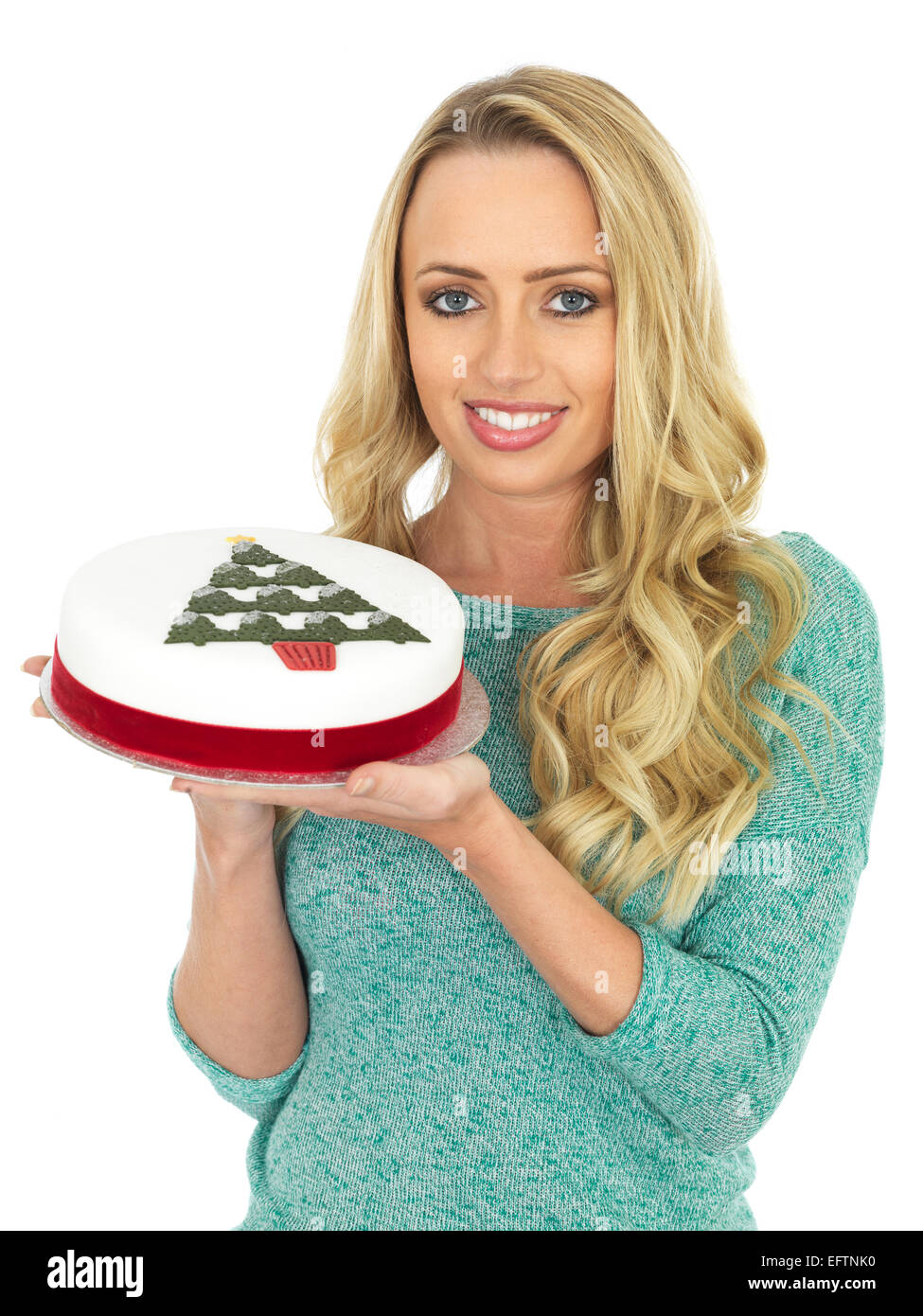 Happy Young Woman Holding A Rich Christmas Fruit Cake Iced And Decorated With A Red Ribbon Isolated Against A White Stock Photo