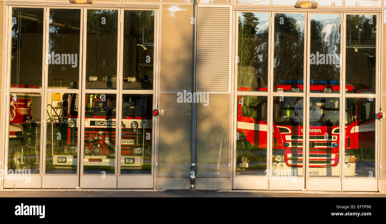 Fire trucks behind glass doors at fire station garage , Finland Stock Photo