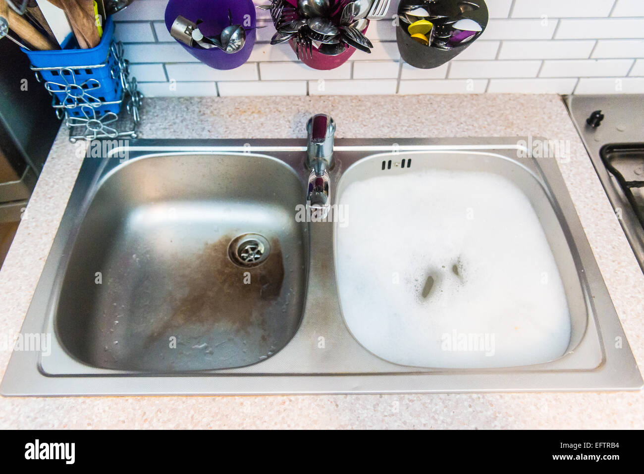 sink with water and white foam - Stock Image