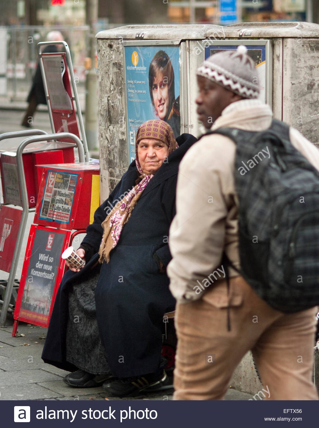 Man Walking Past Elderly Muslim Woman Sitting In Street Holding Empty Coffee Cup Munich Bavaria Germany - Stock Image
