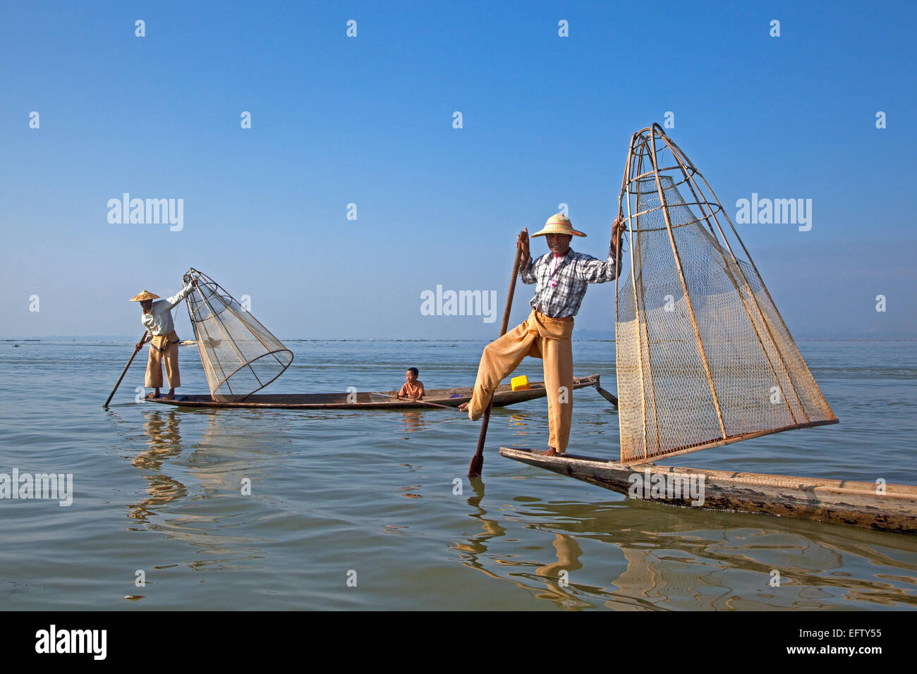Intha fishermen steering traditional fishing boat by wrapping leg around oar, Inle Lake, Nyaungshwe, Shan State, - Stock Image